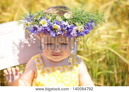 Cute baby girl with wildflower wreath, closeup