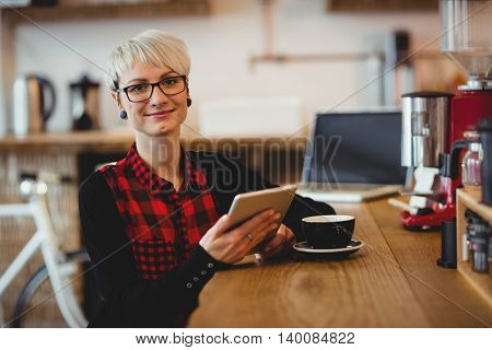 Portrait of happy young woman using digital tablet while having coffee at office cafeteria