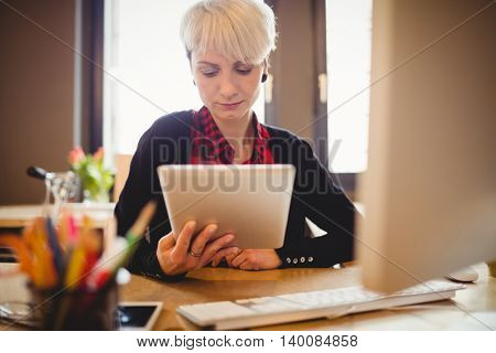 Young woman using digital tablet at office