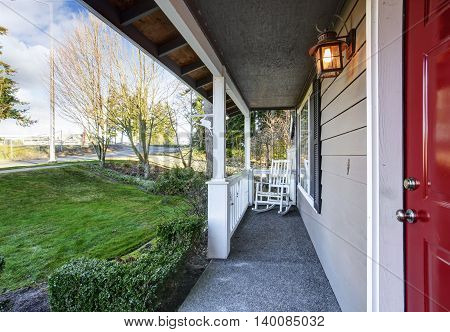 Small Covered Porch With White Rocking Chair And Red Front Door.