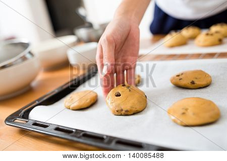 Putting cookies on metal tray before oven