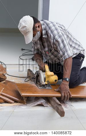 NAKHON RATCHASIMA -JUNE 26 : Carpenter use electric saw to sawing wood board on June 26 2016 in Nakhon Ratchasima Thailand