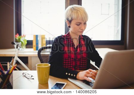 Young woman using laptop at office
