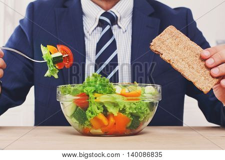 Man in suit unrecognizable torso eating healthy business lunch in modern office interior. Businessman at working place with vegetable salad in bowl, diet and right nutrition concept.