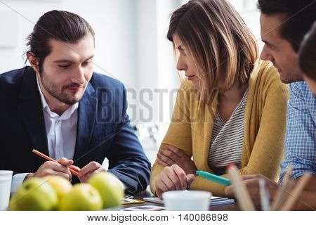 Photo editor explaining to colleagues in meeting room at creative office