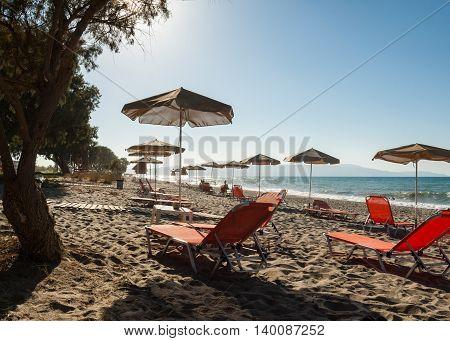 Sun beds and shade umbrellas at a beach on Crete. Greece
