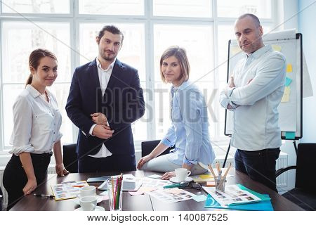 Portrait of confident photo editors in meeting room at creative office