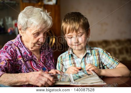 Elderly woman with her little grandson looking album