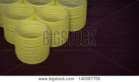 Still life yellow hair curlers on a dark wooden background closeup with copy-space