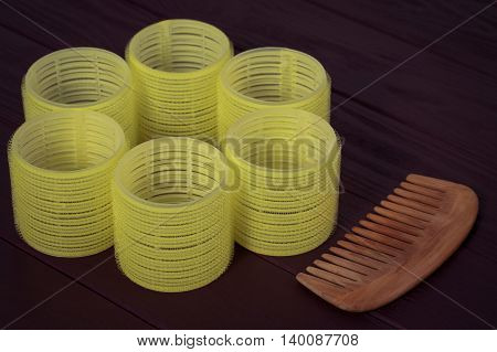 Still life yellow hair curlers with wooden comb on a dark background closeup