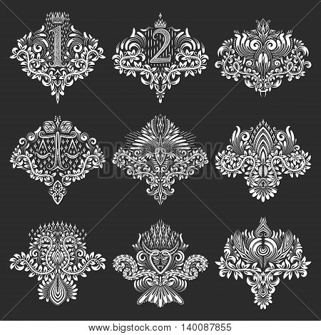 Set of ornamental elements for design in coats of arms form. White floral decorations on black. Isolated tattoo patterns in vintage baroque style.