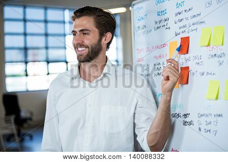 Smiling businessman pointing on sticky note stuck to whiteboard in meeting room