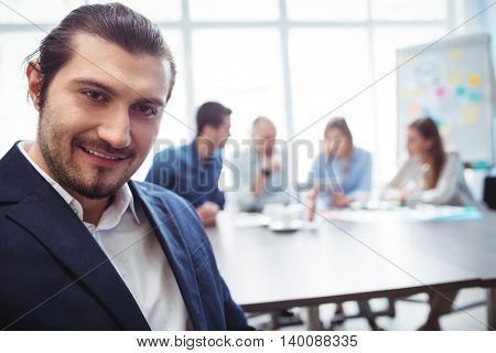 Portrait of smiling businessman against coworkers in meeting room at office
