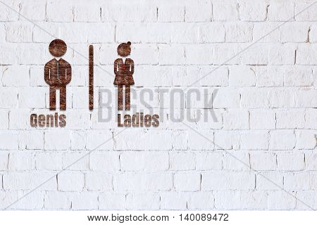 Toilet sign on a white brick background.