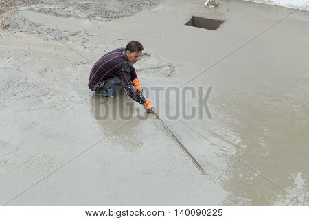NAKHON RATCHASIMA -JULY 6 : Plasterer screed concrete for floor at construction on July 6 2016 in Nakhon Ratchasima Thailand