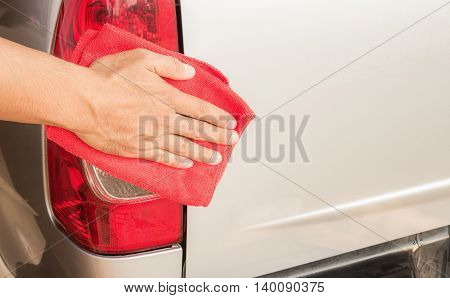 Hand with microfiber cloth cleaning a car.