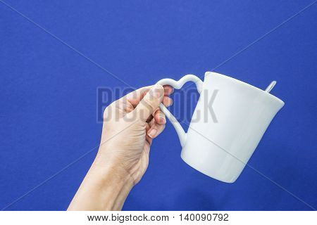 Carry a white mug with heart handle in blue background