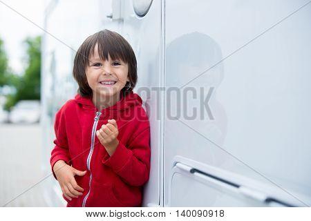 Cute Kid, Sitting On A Doorway Of A Caravan