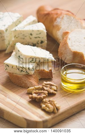 home made cheese and walnuts olive oil and bread on a wooden board. brined curd white cheese with nuts on the table. Delicious food for breakfast or snack
