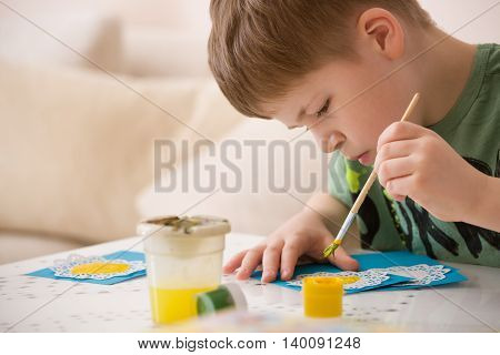 Portrait of little school boy sitting at the table and drawing with yellow paint. After school activities at home. Education. Small boy creating handmade cards.