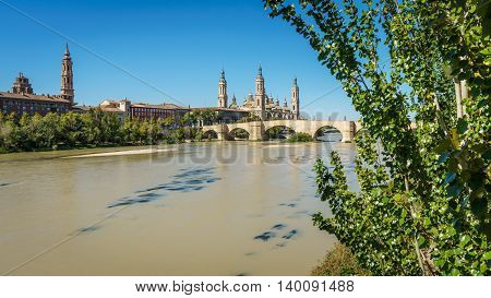 Panoramic view of El Pilar basilica and the Ebro River with tree. Long exposure, silk water