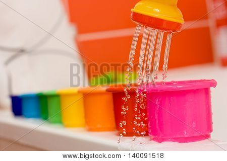 Rainbow with pouring water. Row of colorful bowls and watering from a watering can in the bathroom. Fun with children in bathroom. Activities with kids.