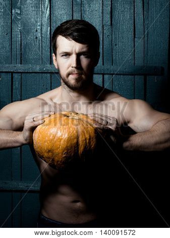 Young man with muscular sexy body and orange Halloween pumpkin