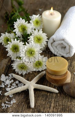 spring flower, pile of salt ,massage oil ,soap,shell on old wood