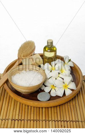 Spa setting in wooden bowl on mat texture