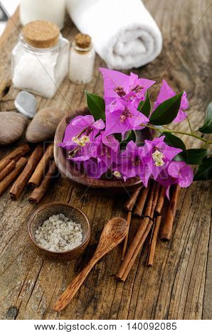 spring flower, pile of saltin bowl ,massage oil ,soap, towel,on old wood