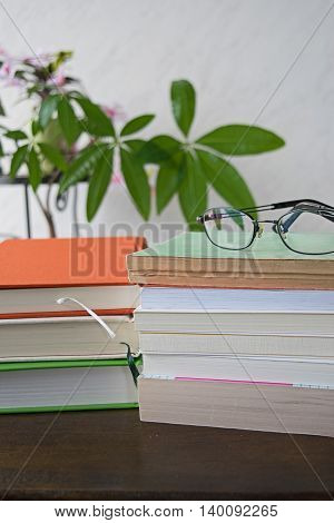 Stack of colorful books with glasses on wooden desk, background