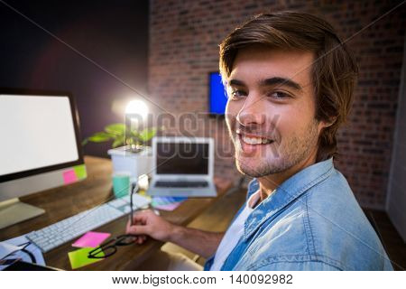 Portrait of smiling young man in creative office