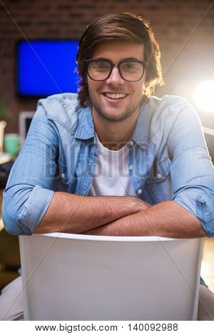 Portrait of smiling young man sitting on chair in creative office