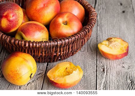 Ripe juicy nectarines in a wicker basket on a gray wooden table.