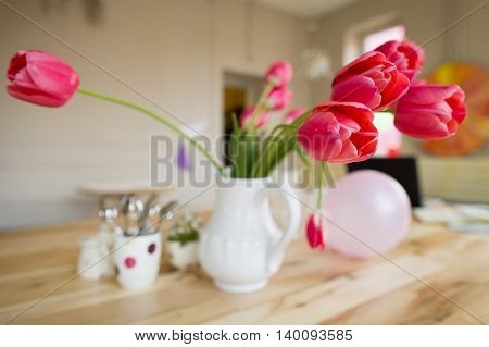 Beautiful table setting with red tulips forget me not and cups on the wooden table.