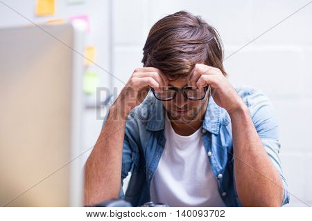 Tensed young man sitting in creative office