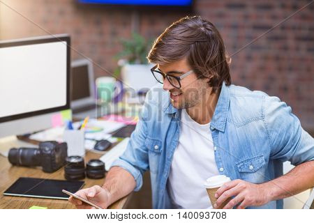 Smiling young man using mobile phone in creative office