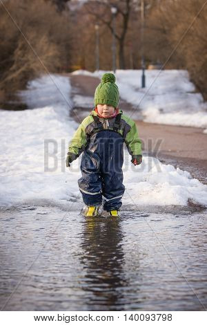 Little cute child in rubber boots running into the puddle and having fun in the spring park. Boy jumping through big puddle. Outdoor activities with children.