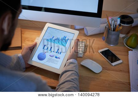 Tablet with business chart in hands of entrepreneur