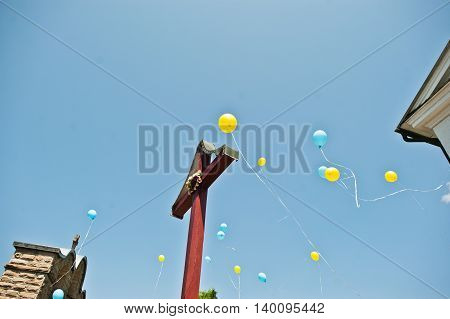Blue And Yellow Balloons At Sky Background Cross At Church.