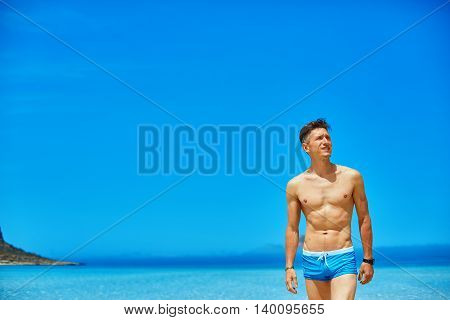 strong athletic man with bared torso standing on the beach along the sea front