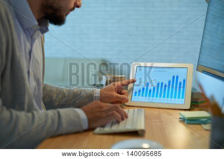 Young financial manager analyzing economics of enterprise
