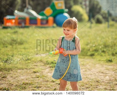 cute little girl playing water gun with hose outside