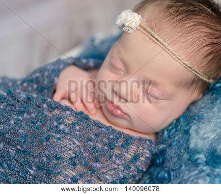 cute newborn baby girl in blue baby soft sleeping