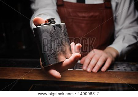 barman holding ice cold flask no face