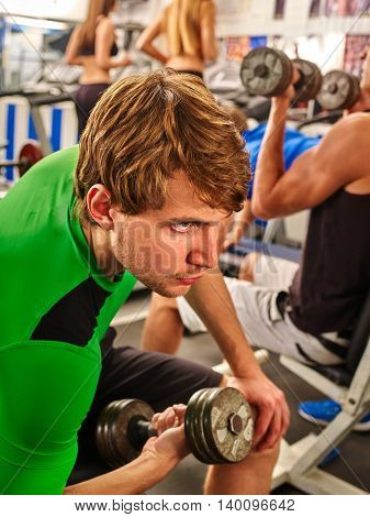 Group of men working with barbell his body at gym. Strong sport man with barbell at sport gym.