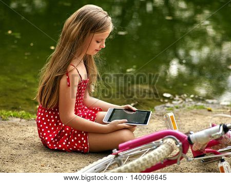Bicycle little girl. Girl wearing red polka dots dress recreation near bicycle into park. Children watch tablet pc. Girl in ecotourism. Girl near river.