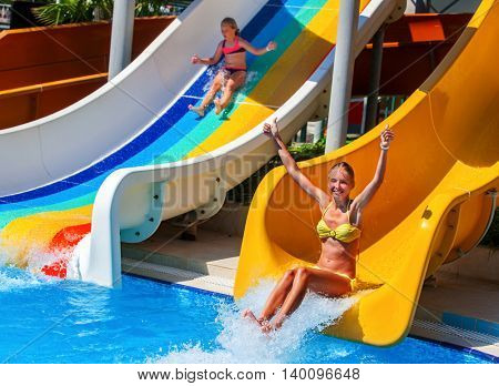 Two children on water slide at water park and thumb up. Summer holiday. There are two water slides in water park. Outdoor.