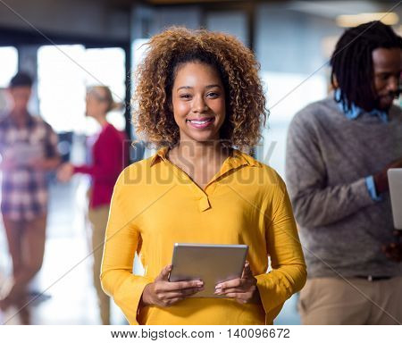 Portrait of smiling woman holding digital tablet in creative office