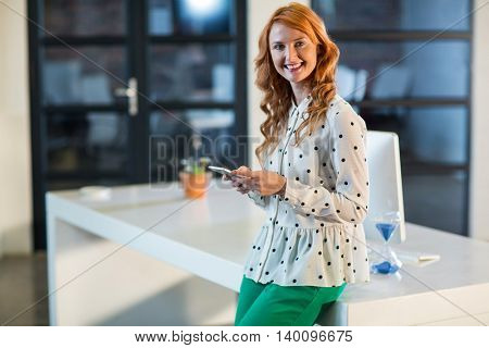 Portrait of smiling young woman using mobile phone in creative office